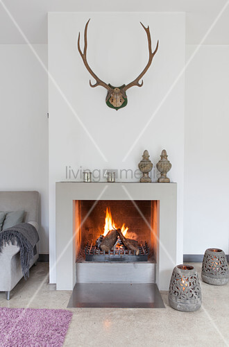Fire in fireplace below antlers on wall