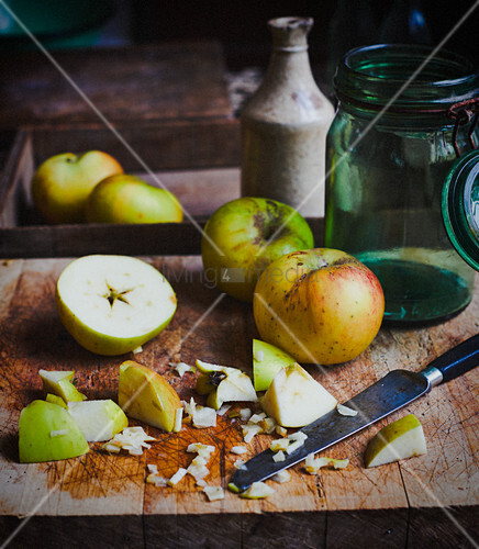 Apples and chopped apples on rustic wooden board