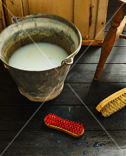 Soapy water in vintage bucket and scrubbing brushes