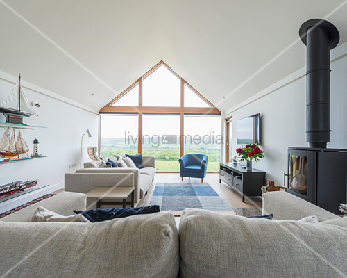 Pale seating and log burner in elegant living room with glass wall