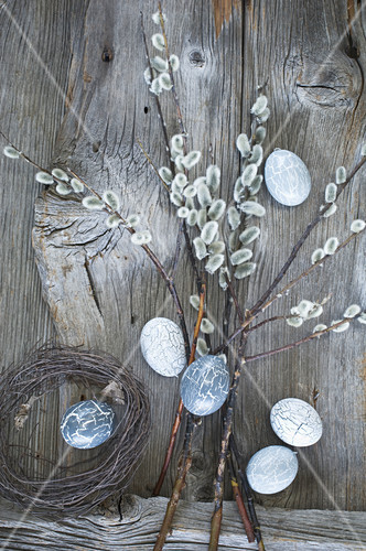 Grey-painted Easter eggs hung from pussy willow branches in bottle