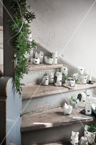 Adventskalender in Gläsern mit Seidenpapier auf der Treppe