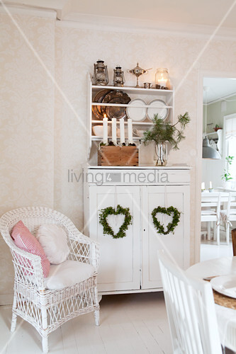 Wicker armchair next to white dresser with Christmas decorations