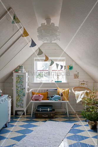 Cushions and soft toys on bench next to cabinet in attic room with blue-and-white chequered floor