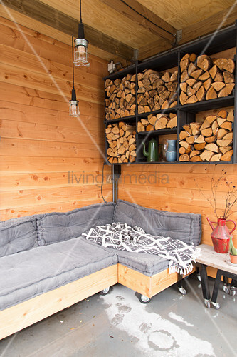 Sofa and side table on castors below firewood stacked in wall-mounted shelves in room with wooden walls