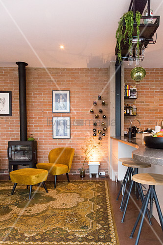 Retro armchair and footstool between log burner and kitchen counter in open-plan interior