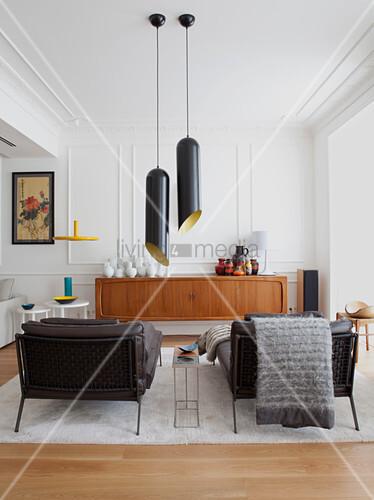 Zwei schwarze Liegen, Pendelleuchten und Sideboard in weißem Wohnzimmer