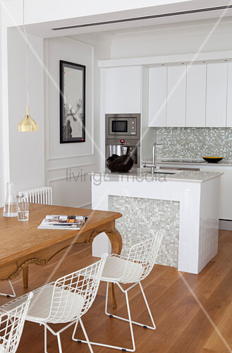 Wooden table and white classic chairs, island counter and white fitted kitchen cabinet in open-plan interior