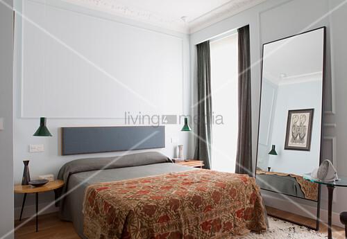 Doppelbett, jadegrüne Pendelleuchten über Beistelltische und Standspiegel im Schlafzimmer