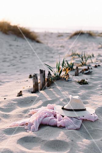 Strohhut und rosa Schal liegen am Strand