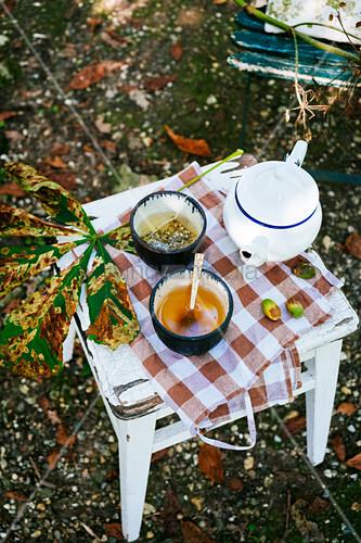 Teekanne mit Teeschalen auf Holzhocker im Garten