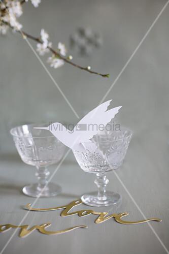 Paper hummingbird in vintage wine glass