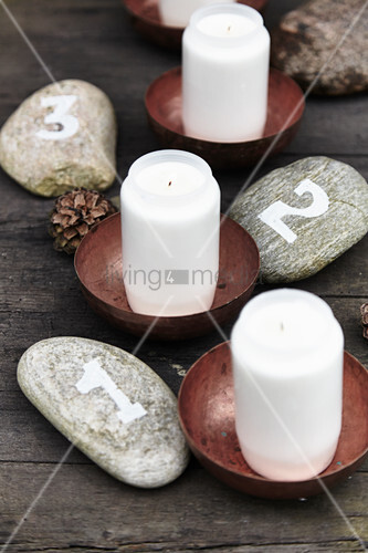 Advent arrangement handmade from numbered pebbles and candles