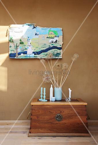 DIY-Collage auf Pappe als Wanddekoration über Truhe mit Kerzen und Trockenblume