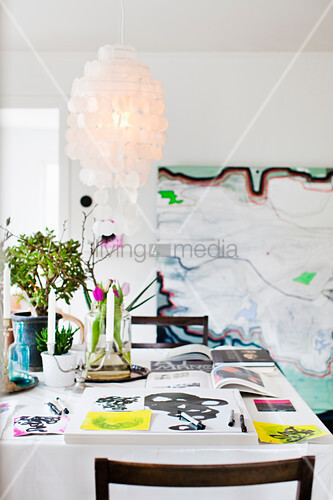 Books, painting utensils, candles and flowers on dining table