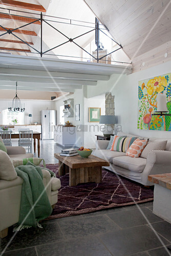 Open-plan Mediterranean interior with gallery and exposed roof structure