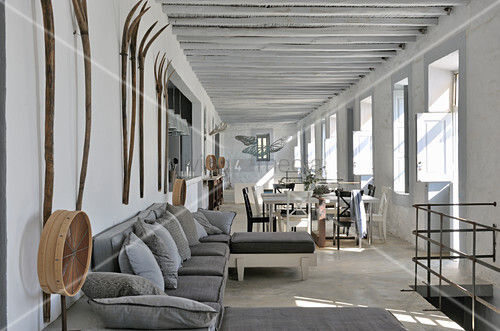 Open-plan interior in shades of grey with wooden ceiling beams and rustic accessories