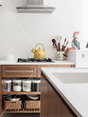 Storage jars on base-unit shelves and kettle on gas hob seen across island counter
