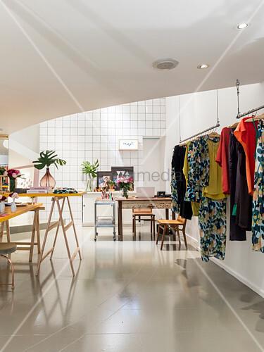 Garderobenständer mit Damenkleidung, im Hintergrund Schreibtisch in offener Raum