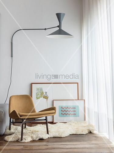 Designerstuhl auf Tierfellteppich, Bilder an der Wand und Wandleuchte vor Fenster mit Vorhang