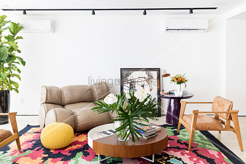 Designer seating around small, low table in living room