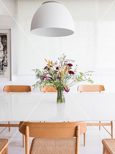 Holzstühle um weißen Esstisch mit Blumenstrauß, darüber weiße Lampe