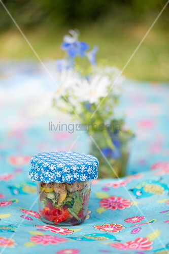 Marinated vegetables in jar with handmade oilcloth cover