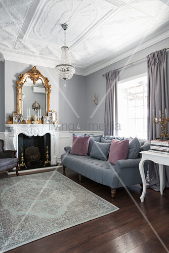 Grey sofa, gilt-framed mirror above fireplace and stucco ceiling in elegant living room