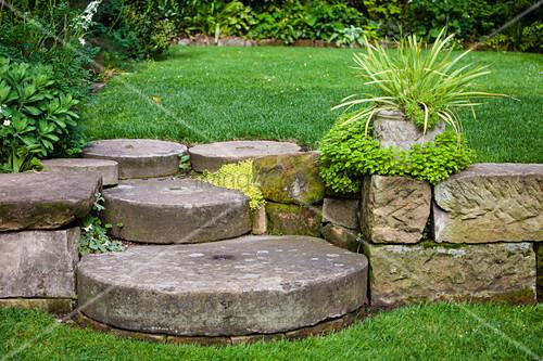 Alte Mühlsteine als Stufen im Garten mit verschiedenen Ebenen