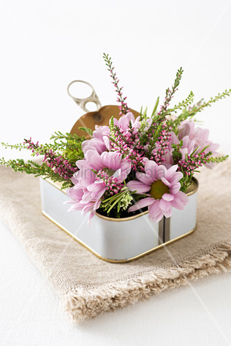 Pink flower arrangement in sardine tin decorating table