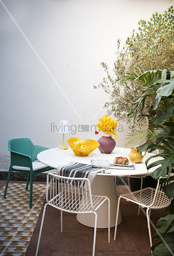 Round table against white wall on Mediterranean terrace