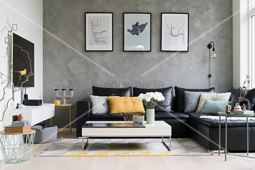 Black leather couch and coffee table in open-plan interior with grey wall