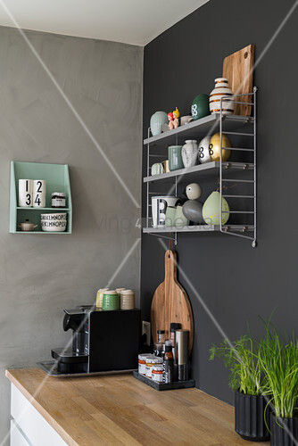 Wall-mounted shelves above coffee machine on wooden worksurface in kitchen