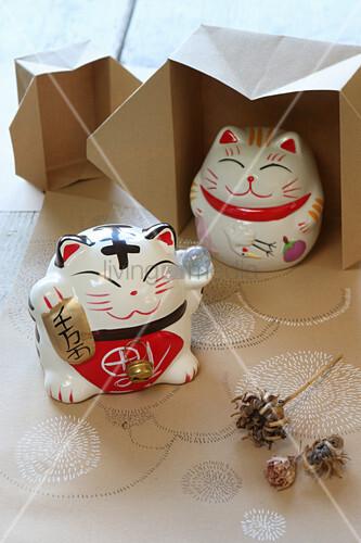 Asiatische Katzen aus Keramik auf bemaltem Papier