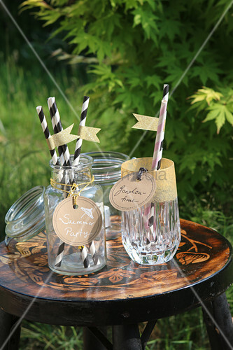 Hand-crafted tags on drinking glasses with paper straws