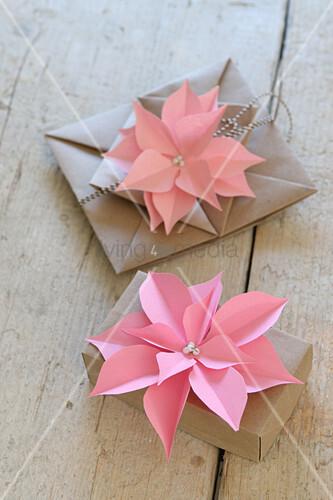 Rosafarbene Papierblumen auf verpackten Geschenken