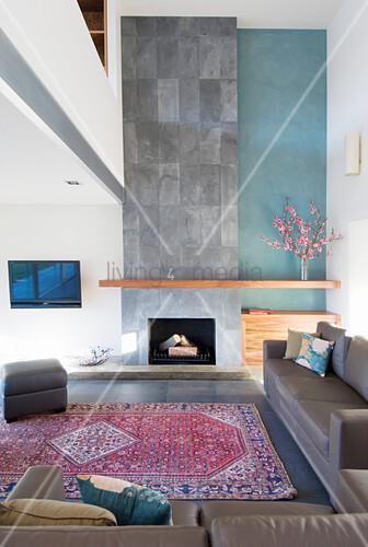 Graue Ledergarnitur und Kamin mit raumhoher Betonwand in der Lounge