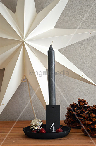 Candlestick labelled with number 4 and pine cones in front of star-shaped lamp on wall