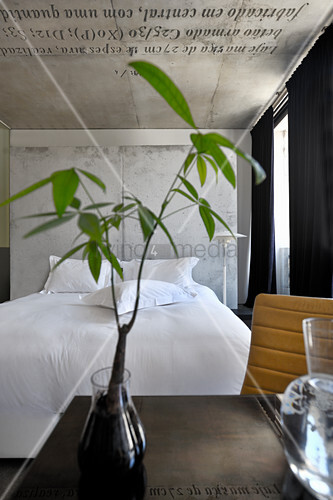 View past leafy branches in vase on table to double bed with white bed linen against concrete partition