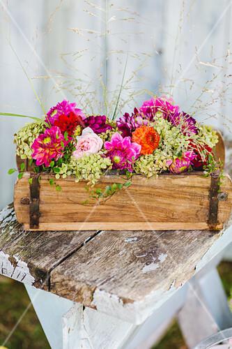 Gesteck mit Dahlien, Hortensien, Gräsern und Mühlenbeckia im Holzkästchen