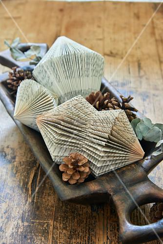 Prismen aus gefalteten Büchern in einem Holztrog mit Zapfen
