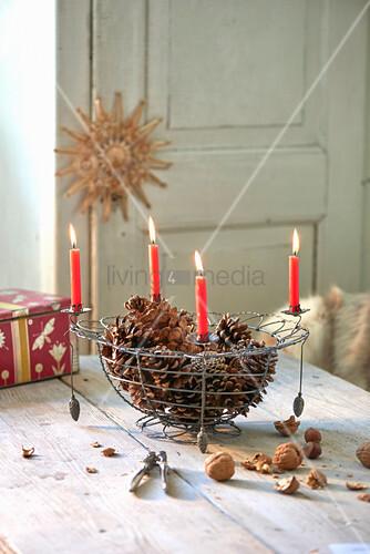 Zapfen im Drahtkorb mit vier brennenden roten Kerzen