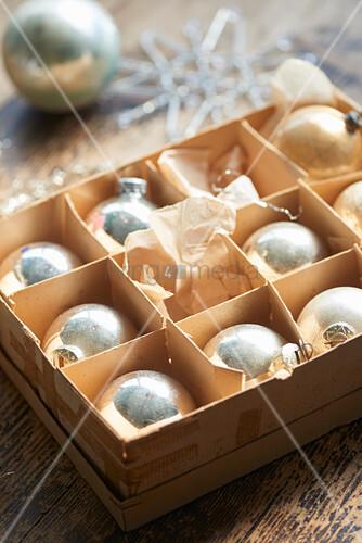 Alte silberne Weihnachtskugeln in einer Pappschachtel