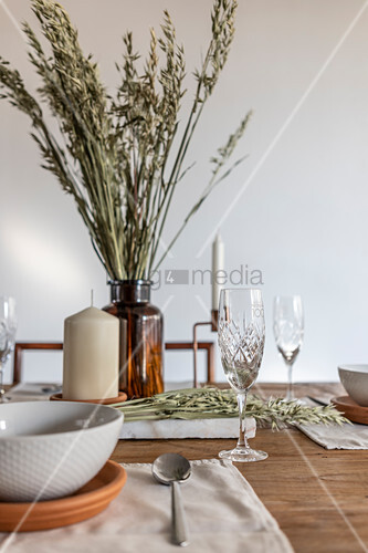 Wooden table set with candle and ears of cereal in apothecary bottle