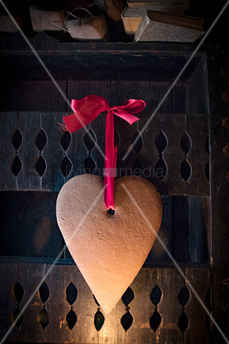 Festive gingerbread heart hung from red ribbon