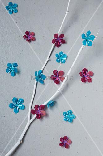 Zweige mit Papierblüten dekoriert