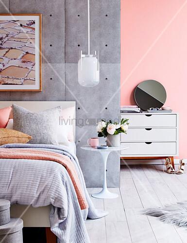 Bett an Raumteiler mit Beton-Tapete im pastellfarbenen Schlafzimmer