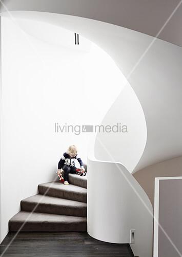 Junge spielt auf organisch geformter, gemauerter Treppe