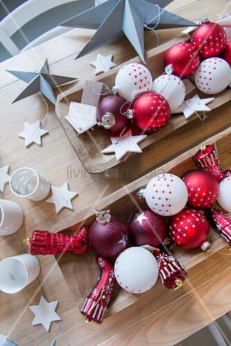 Rote und weiße Christbaumanhänger in Holztrögen auf dem Tisch