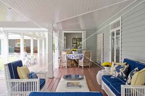 Sitzgruppe und Esstisch mit blau-gelber Deko auf der Veranda